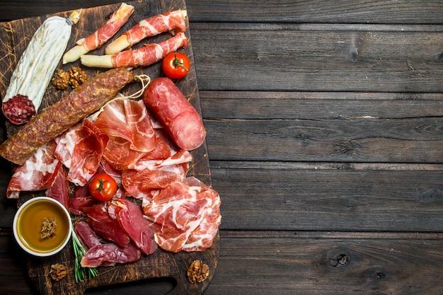 Antipasto. variedade de salgadinhos de carne no quadro. em uma madeira.