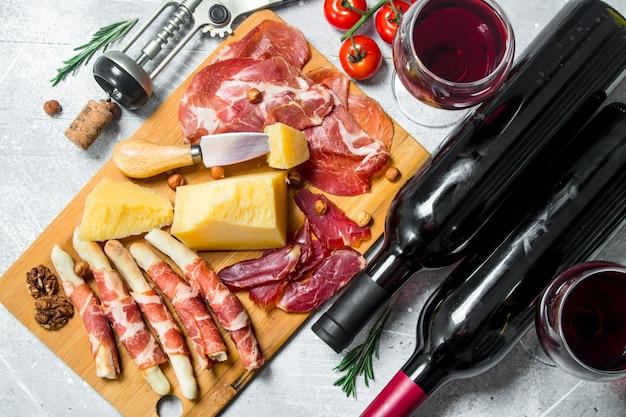 Antipasto. vários petiscos de carne e queijo com vinho tinto. em um rústico.