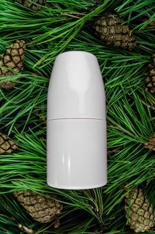 Antiperspirant do modelo em um fundo roxo. ramos e cones do abeto - cosméticos naturais.