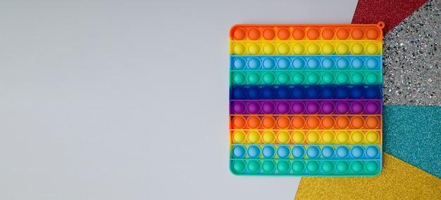 Antistress de brinquedo de silicone de arco-íris de vista superior pop-lo sobre fundo colorido. faixa popular de brinquedo sensorial para crianças