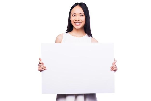 Anunciando seu produto. mulher jovem e bonita asiática segurando o espaço da cópia e sorrindo em pé contra um fundo branco