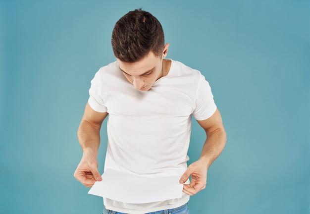 Anunciante masculino com uma folha de papel branca em um panfleto de maquete de fundo azul. foto de alta qualidade