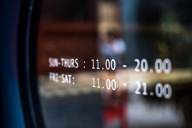 Anúncio de horário comercial em uma janela