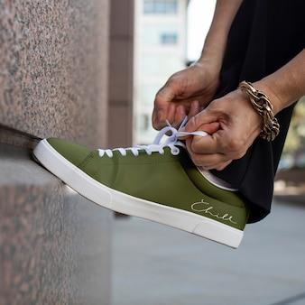 Anúncio de roupas modelo verde de tênis de lona amarrando cadarços