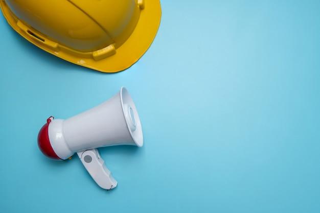 Anúncio e anunciar relações públicas de parede de publicidade sobre construção civil, casa, casa e imóveis com megafone e capacete amarelo na parede azul