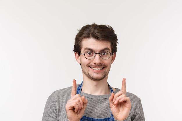 Anúncio, pequenas empresas e conceito de carreira. retrato de close-up de sorriso entusiasmado, animado barista masculino, barman apontando para cima e sorrindo câmera, convidar a visitar sua cafeteria, tente-se