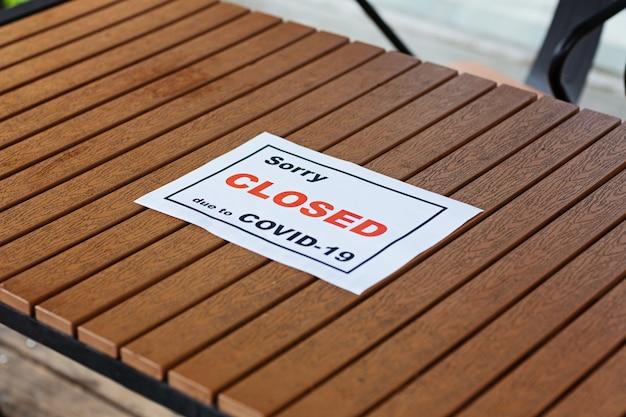 Anúncio pesaroso fechado devido a covid-19 na mesa do café. pandemia do coronavírus. desligamento do governo