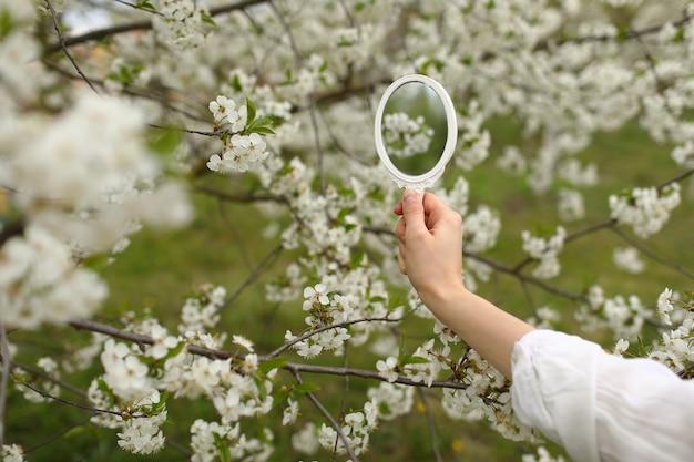Ao ar livre, close-up da jovem mão feminina segurando um pequeno espelho retrô no jardim florescendo na primavera.