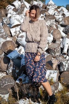 Ao ar livre close-up retrato de uma jovem mulher bonita uma camisola de tricô, lindo vestido e botas posando, desfrutando de um dia quente de outono