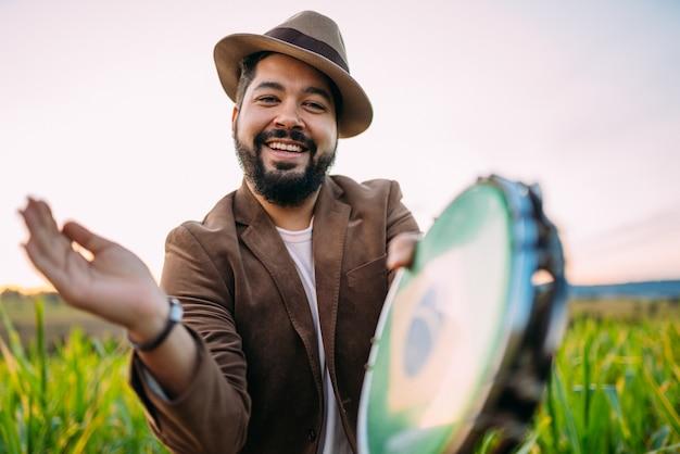 Ao ar livre de um jovem latino-americano tocando pandeiro. músico brasileiro.