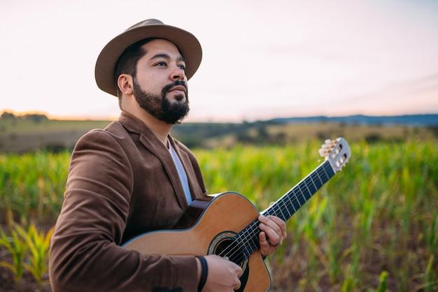 Ao ar livre de um jovem latino-americano tocando violão. músico brasileiro.