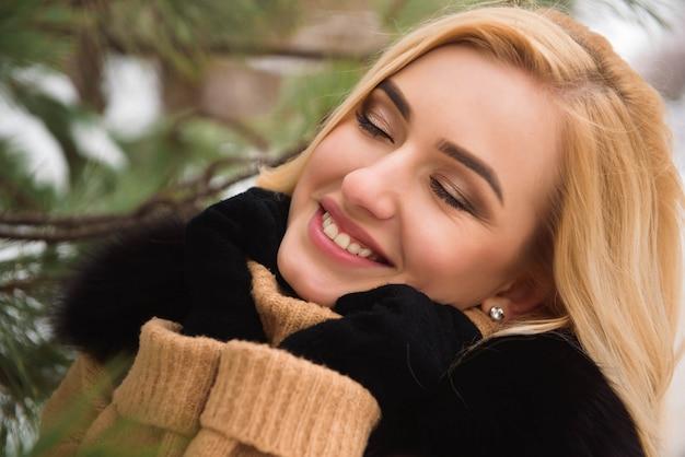 Ao ar livre feche a foto da bela jovem sorridente feliz andando na rua no inverno