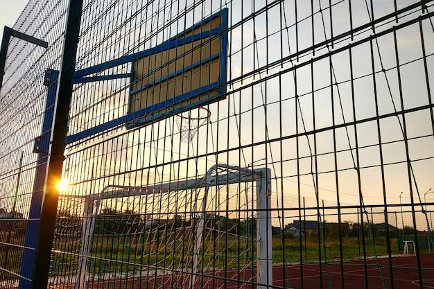 Ao ar livre mini quadra de futebol e basquete com portão bola e cesta cercada com alta cerca de proteção.