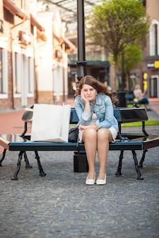 Ao ar livre, uma mulher triste sentada no banco com uma sacola de papel