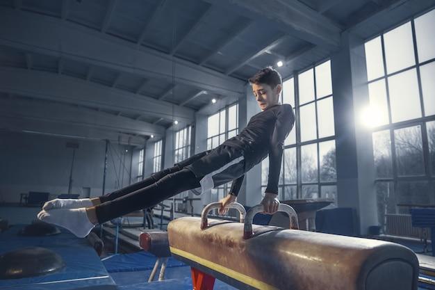 Ao controle. pequeno ginasta masculino treinando no ginásio, flexível e ativo. menino caucasiano, atleta em roupas esportivas, praticando exercícios para fortalecer e equilibrar. movimento, ação, movimento, conceito dinâmico.