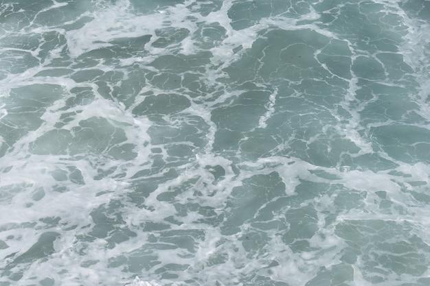 Ao fundo, a água azul espuma