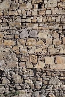 Ao fundo, muitas pedras repousam umas sobre as outras, uma parede de pedra.