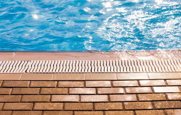 Ao lado da piscina com água cristalina e cristalina sob a luz do sol na base para relaxar, fotografe em close-up