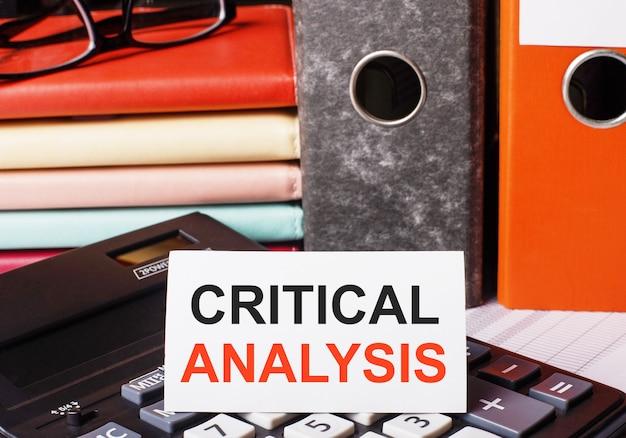 Ao lado das agendas e pastas com documentos na calculadora há um cartão branco com a inscrição análise crítica