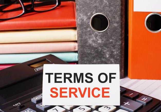 Ao lado das agendas e pastas com documentos na calculadora há um cartão branco com a inscrição termos de serviço