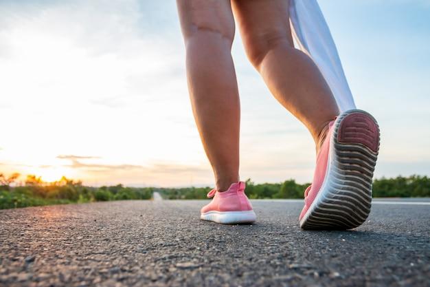 Ao longo da estrada, na área da colina, na hora do pôr do sol, a mulher está se exercitando correndo.