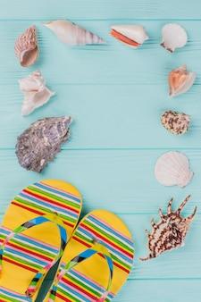 Ao longo do perímetro estão diferentes conchas do mar e sandálias brilhantes no canto sobre fundo turquesa. copie o espaço no centro.