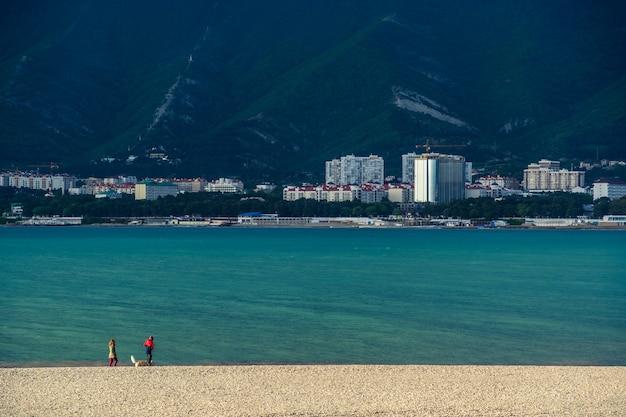 Ao pôr do sol, uma mulher, um homem e um cachorro caminham em uma praia de seixos