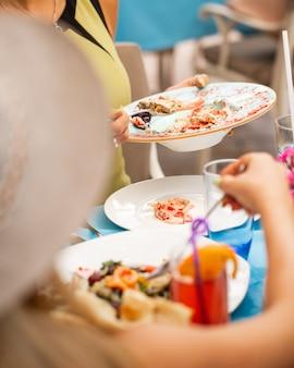 Ao redor da mesa de jantar, levando comida em chapa branca.