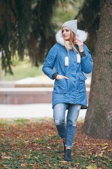Apaixonada pela natureza, uma garota com uma jaqueta caminha pelo parque de outono.