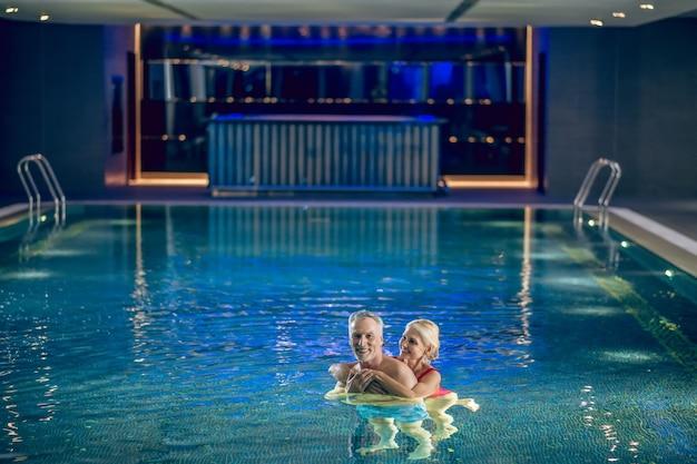 Apaixonado. casal passando um tempo em uma piscina e parecendo romântico