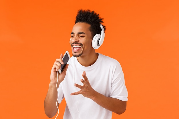 Apaixonado e despreocupado cara afro-americano sonhando se tornar cantor de verdade, segurando o telefone e cantando no celular como jogando app de karaokê, usando fones de ouvido, parede laranja