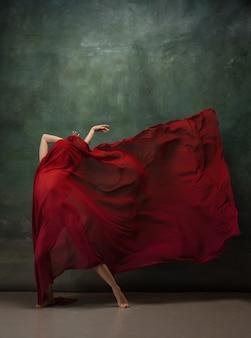 Apaixonado em movimento. graciosa bailarina clássica dançando no fundo escuro do estúdio. pano vermelho intenso. o conceito de graça, artista, movimento, ação e movimento. parece leve, flexível. estilo fashion.
