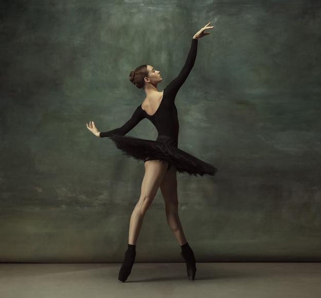 Apaixonado. graciosa bailarina clássica dançando, posando isolada na parede escura do estúdio