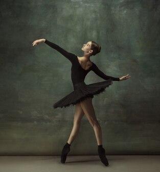 Apaixonado. graciosa bailarina clássica dançando, posando isolada no fundo escuro do estúdio. elegance tutu preto. conceito de graça, movimento, ação e movimento. parece leve, flexível. elegante.
