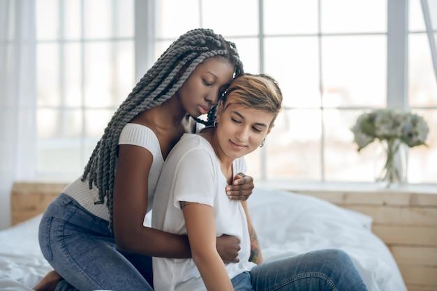Apaixonado. menina de pele escura abraçando a namorada de cabelo curto nas costas e parecendo terna