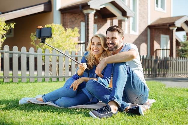 Apaixonado para sempre. casal fofo de meia-idade sentado no tapete no quintal, abraçando e tirando uma selfie com a ajuda de um bastão de selfie