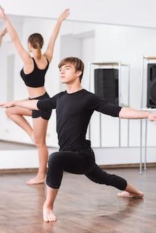 Apaixonado por coreografia. dançarino bonito, gracioso e bem construído, abrindo os braços e olhando para a frente enquanto faz um treino de dança