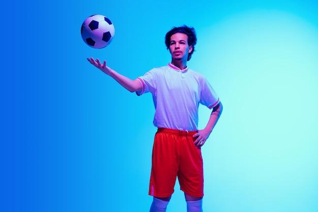 Apaixonado por jogos de futebol ou jogador de futebol em fundo de estúdio azul gradiente em neon
