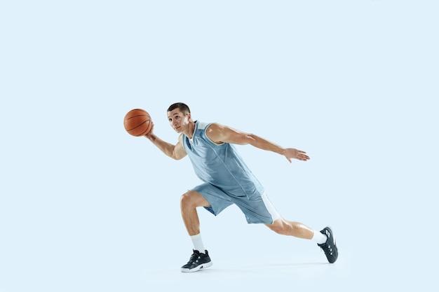 Apaixonado por. jovem jogador de basquete caucasiano da equipe em ação, movimento em salto isolado sobre fundo azul. conceito de esporte, movimento, energia e estilo de vida dinâmico e saudável. treinando, praticando.