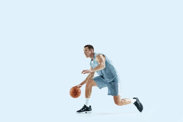 Apaixonado por jovem jogador de basquete caucasiano do time em ação, movimento em salto isolado