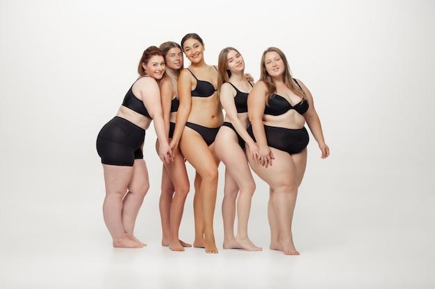 Apaixonado por mim mesmo. retrato de mulheres bonitas com diferentes formas, posando em fundo branco. modelos femininos felizes. conceito de corpo positivo, beleza, moda, estilo, feminismo. diversidade.