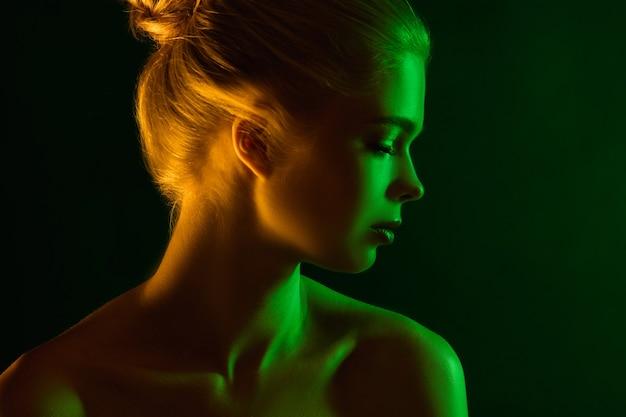 Apaixonado. retrato do modelo feminino em luz de néon no fundo escuro do estúdio. linda mulher caucasiana com maquiagem da moda e pele bem cuidada. estilo vívido, conceito de beleza. fechar-se. copyspace