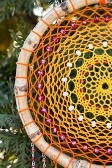Apanhador de sonhos artesanal com fios de penas e contas de corda pendurada