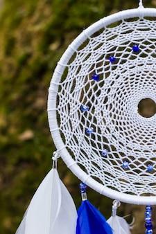 Apanhador de sonhos azul e branco feito de contas e cordas de couro de penas, pendurado