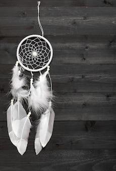 Apanhador de sonhos brancos na superfície de madeira