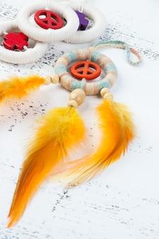 Apanhador de sonhos brilhantes com um sinal de paz laranja