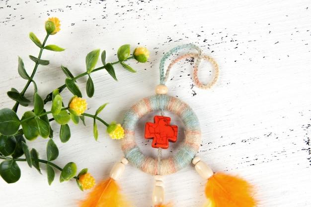 Apanhador de sonhos brilhantes com uma cruz laranja