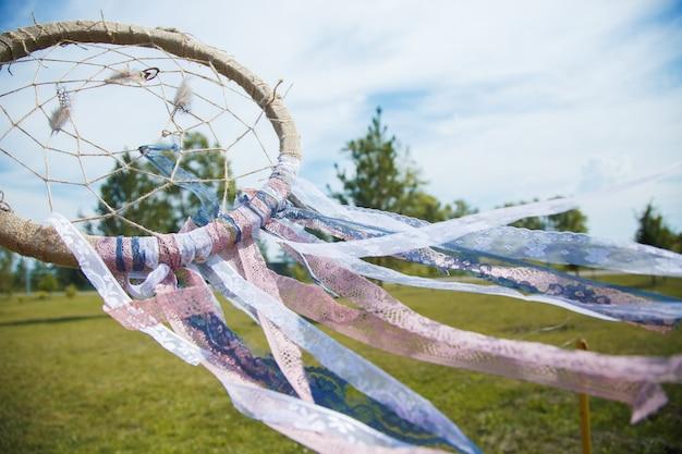 Apanhador de sonhos close-up sobre um fundo de relva verde e céu azul