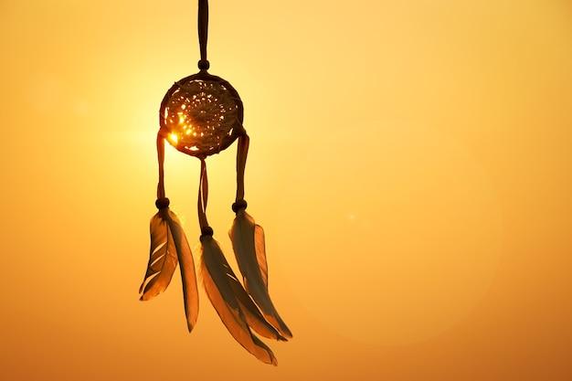 Apanhador de sonhos com fio de pena branca e cordão de miçangas apanhador de sonhos feito à mãoa luz do conjunto.