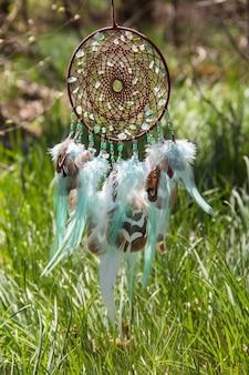 Apanhador de sonhos com fios de penas e cordões de miçangas pendurados
